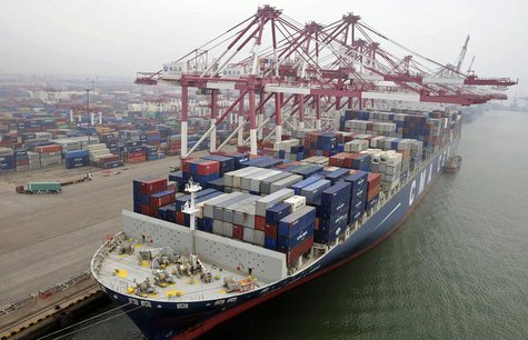 A cargo ship loaded with containers is seen anchored at a port in Qingdao, Shandong province July 10, 2013. China's exports in June declined
