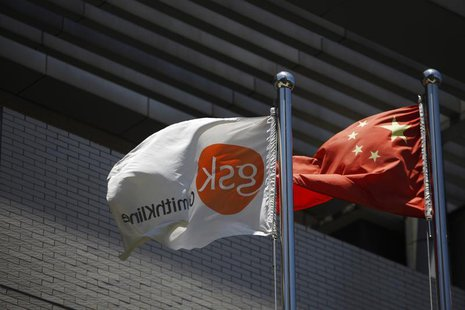 A flag (L) bearing the logo of GlaxoSmithKline (GSK) flutters next to a Chinese national flag outside a GlaxoSmithKline office building in S