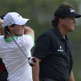 Rory McIlroy of Northern Ireland (L) tees off on the sixth hole as Phil Mickelson of the U.S. watches during the first round of the British