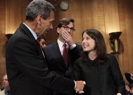 Representative Mel Watt (L), nominee to be the regulator of mortgage finance firms Fannie Mae and Freddie Mac, shakes hands with Kara Stein,