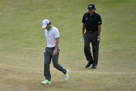 Rory McIlroy of Northern Ireland (L) walks off the fourth green after his bogey putt followed by Phil Mickelson of the U.S. during the first