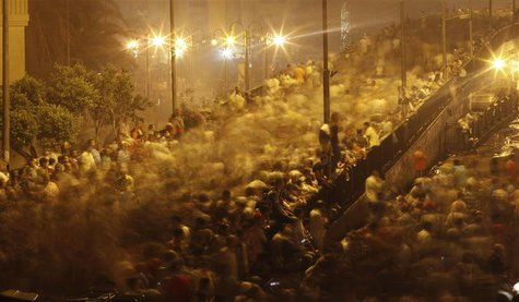 Supporters of deposed Egyptian President Mohamed Mursi run from tear gas fired by riot police during clashes on the Sixth of October Bridge