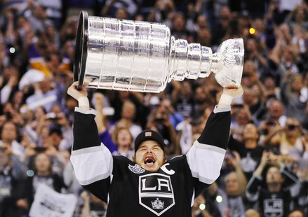 Los Angeles Kings captian Dustin Brown hoists the Stanley Cup after his team defeated the New Jersey Devils during Game 6 of the NHL Stanley