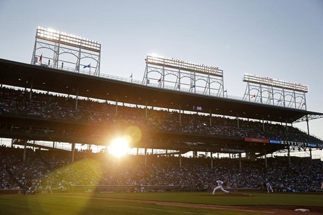 Chicago Cubs' Edwin Jackson (R) pitches against St. Louis Cardinals' Pete Kozma as the sun sets during the third inning of their National Le