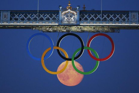 The full moon rises through the Olympic Rings hanging beneath Tower Bridge during the London 2012 Olympic Games August 3, 2012. REUTERS/Luke