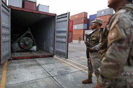 Panama police officers stand guard in front of a container holding a green missile-shaped object seized from the North Korean flagged ship ''Chong Chon Gang'' at the Manzanillo Container Terminal in Colon City July 17, 2013. Credit: Reuters/Carlos Jasso