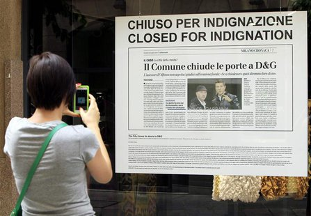 A girl takes a picture of the windows of a Dolce&Gabbana closed store, displaying a newspaper article as a protest in downtown Milan July 19