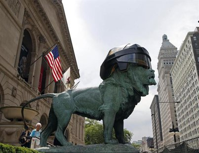 A woman walks past one of the bronze lion statues in front of the Art Institute of Chicago that was fitted with an oversized hockey helmet i