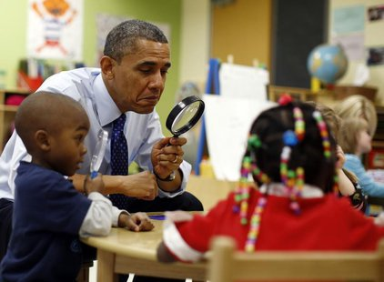 U.S. President Barack Obama uses a magnifying glass to play a game with children in a pre-kindergarten classroom at College Heights early ch