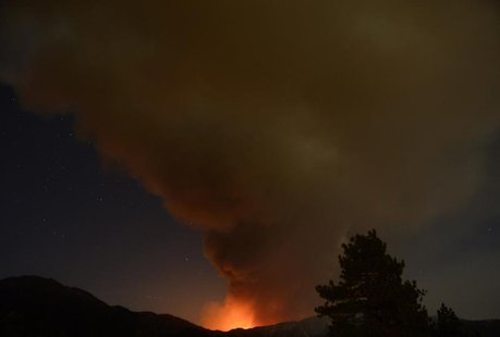 A plume of smoke rises into the night sky as a wildfire, or the so-called Mountain Fire, burns near Idyllwild, California July 18, 2013. REU
