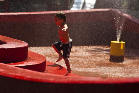A boy plays with water during a hot day in New York July 19, 2013. REUTERS/Eduardo Munoz