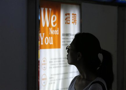 A job seeker looks at a job advertisement board at a Beijing talent service centre July 17, 2013. Picture taken July 17, 2013. REUTERS/Kim K