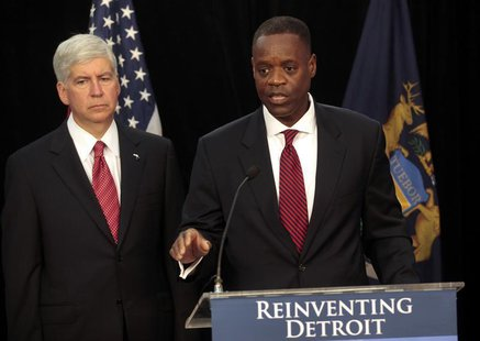 Detroit Emergency Manager Kevyn Orr (R) addresses the media as Michigan Governor Rick Snyder listens during a news conference about filing b