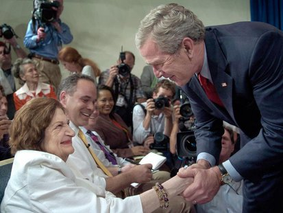 U.S. President George W. Bush greets veteran reporter Helen Thomas (L) during a surprise visit to a briefing in the press briefing room of t