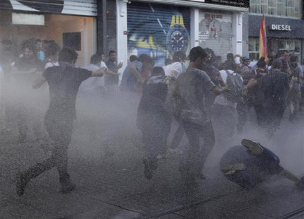 Anti-government protesters take cover as riot police use water cannon to disperse them at Taksim square in central Istanbul July 20, 2013. R