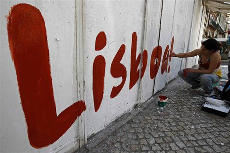 "A political activist paints the word ""Lisbon"" on a wall at a street in Lisbon July 20, 2013. REUTERS/Jose Manuel Ribeiro"
