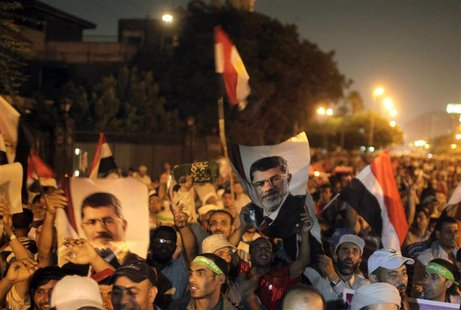 Supporters of deposed Egyptian president Mohamed Mursi hold up Egyptian national flags and posters of Mursi, as they chant slogans during a
