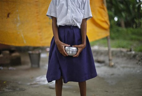 A school girl holds a container to receive her free mid-day meal, distributed by a government-run primary school, at Brahimpur village in Ch