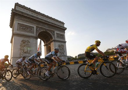 The pack of riders including Team Sky rider and leader's yellow jersey holder Christopher Froome of Britain cycles past the Arc de Triomphe