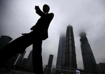 A businessman looks at his mobile phone as he walks in the financial area of Pudong in Shanghai May 30, 2013. REUTERS/Carlos Barria
