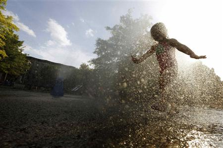 A girl cools off in the water from a playground sprinkler in the Brooklyn borough of New York July 15, 2013. REUTERS-Brendan McDermid