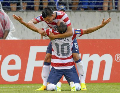 Landon Donovan of the U.S. is embraced by teammate Joe Corona after scoring a goal during the second half of their CONCACAF Gold Cup quarter