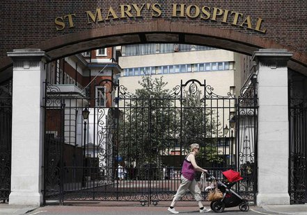 A woman pushes a baby pram past St Mary's Hospital, whose Lindo Wing is where Britain's Catherine, Duchess of Cambridge is expected to give
