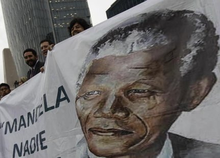 Well-wishers hold a giant banner with an image of former South African President Nelson Mandela during a celebration to mark Mandela's 95th