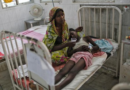 A sick boy lies on his mother's lap inside a hospital after he consumed contaminated meals given to children at a school on Tuesday, in the