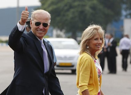 U.S. Vice President Joe Biden gestures as he and his wife Jill (R) arrive at the airport in New Delhi July 22, 2013. Biden is on a four-day