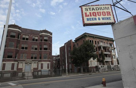 Two vacant and boarded up apartment buildings sit across from a liquor store near downtown Detroit, Michigan July 21, 2013. REUTERS/ Rebecca