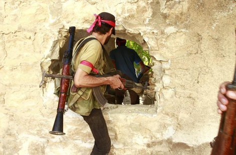 Free Syrian Army fighters move through a hole in a wall in the northern town of Khan al-Assal, after seizing it July 22, 2013. REUTERS/Hamid