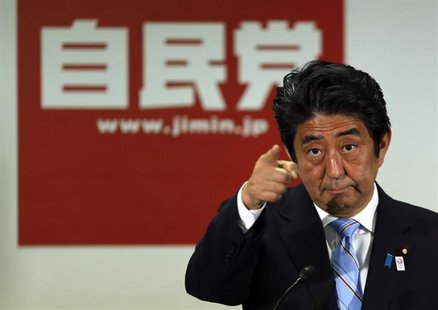 Japan's Prime Minister and the leader of the ruling Liberal Democratic Party (LDP), Shinzo Abe, points to a reporter during a news conferenc
