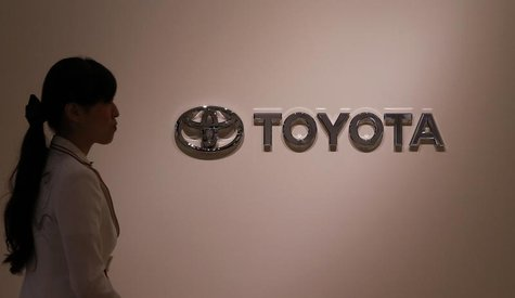 A woman walks past Toyota Motor's logo at the company showroom in Nagoya, central Japan July 1, 2013. REUTERS/Toru Hanai