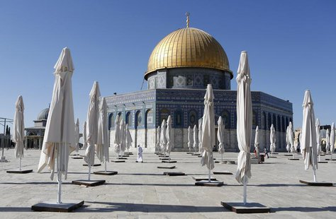 "Palestinians walk amongst parasols placed outside the Dome of the Rock on the compound know to Muslims as ""al-Haram al-Sharif"" and to Jews a"