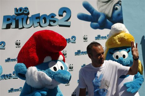 Spain's soccer player Andres Iniesta waves to the crowd during a photocall with two smurf costumed characters during the promotional event f