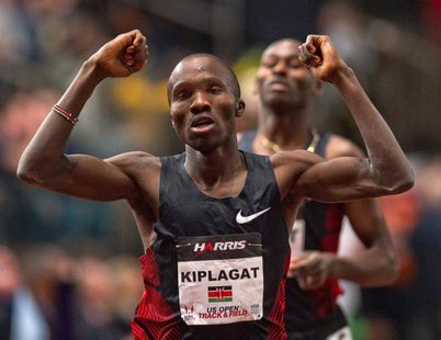 Silas Kiplagat of Kenya reacts at the finish line after beating Bernard Lagat (rear) of the U.S. in the men's 1 mile run at the US Open Trac