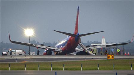 A Southwest Airlines Boeing 737 sits on the tarmac at LaGuardia airport, after making an emergency landing without its nose gear, in New York July 22, 2013.  REUTERS/Carlo Allegri