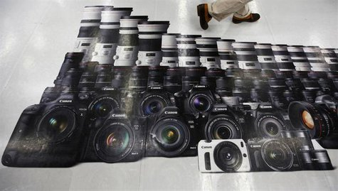 A man walks on an advertisement of Canon digital cameras at an electronics retail store in Tokyo July 24, 2013.REUTERS/Issei Kato