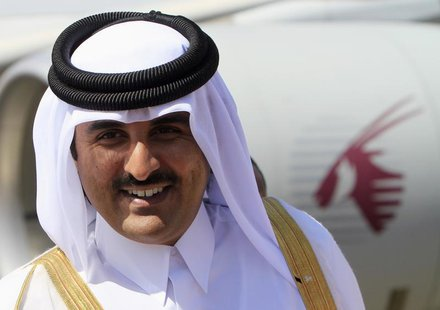 Qatar's Crown Prince Sheikh Tamim Bin Hamad Al Thani smiles during his arrival for an economic ties visit at Khartoum Airport December 4, 20