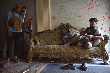 A Free Syrian Army fighter rests on a sofa as a fellow fighter stands near him inside a house in Deir al-Zor July 23, 2013. Picture taken Ju