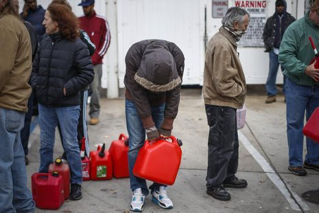 A man stands exhausted while waiting for over five hours to receive fuel from a gas station in Queens, a borough in New York which was left