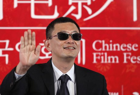 "Director Wong Kar-wai waves during a news conference to promote his movie ""The Grandmaster"", the opening film of the Chinese Film Festival,"