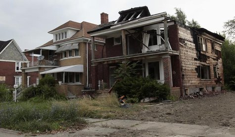 A vacant blighted home is seen next to a well-kept occupied home on West Grand Boulevard in Detroit, Michigan July 23, 2013. REUTERS/ Rebecc