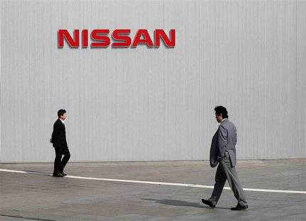 Men walk past a Nissan Motor Co logo at the company's global headquarters in Yokohama, south of Tokyo in this February 9, 2011 file photo. R