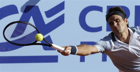 Switzerland's Roger Federer returns the ball to Germany's Daniel Brands during their Swiss Open second round tennis match in Gstaad July 25,