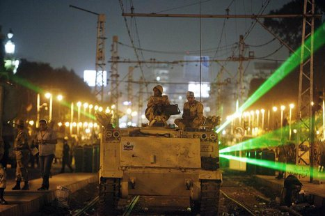 Egyptian Army soldiers sit on an armoured personnel carrier (APC) on a tram track, during a patrol, as supporters of deposed president Moham
