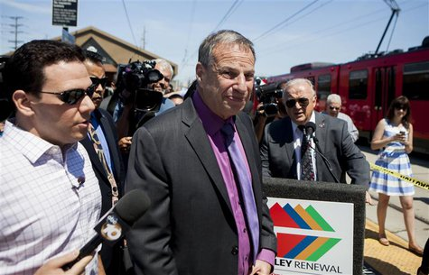 San Diego mayor Bob Filner (C), is surrounded by reporters as he attends a ground breaking ceremony for improvements for the San Diego Troll