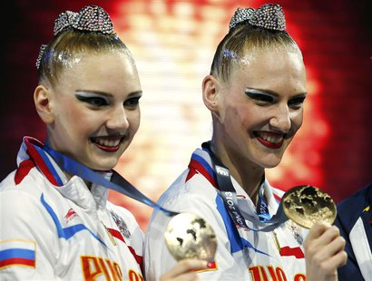Russia's Svetlana Kolesnichenko and Svetlana Romashina (R) pose with their gold medals at the synchronised swimming duet free victory ceremo