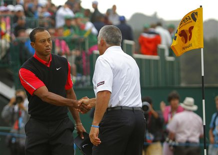 Tiger Woods of the U.S. (L) shakes hands with his former caddie Steve Williams, after finishing his final round of the British Open golf cha